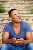 Hombre africano joven que se sienta afuera usando el teléfono elegante y que mira para arriba Fotografía de archivo libre de regalías