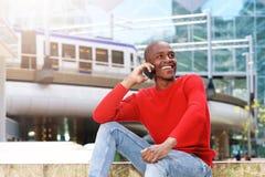 Hombre africano joven que se sienta afuera usando el teléfono móvil Fotos de archivo libres de regalías