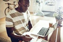 Hombre africano joven que trabaja en un escritorio en una oficina imagenes de archivo