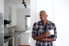 Hombre africano joven relajado que come una taza de café en casa Fotografía de archivo libre de regalías