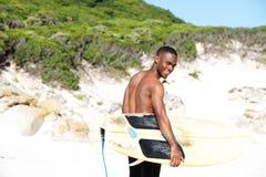 Hombre africano joven sonriente con la tabla hawaiana Fotografía de archivo libre de regalías