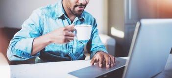 Hombre africano joven sonriente que hace la conversación video vía el ordenador portátil con los socios mientras que bebe té negr fotos de archivo libres de regalías