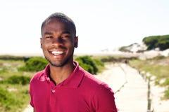 Hombre africano joven sonriente que se coloca al aire libre Foto de archivo