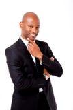 Hombre africano profesional feliz que sonríe tocando su barbilla Foto de archivo