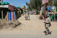 Hombre africano que camina más allá de un mercado ocupado en una calle secundaria Fotos de archivo