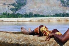Hombre africano que descansa en canoa tradicional Imagen de archivo libre de regalías