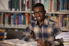 Hombre africano que estudia en una biblioteca Imagenes de archivo
