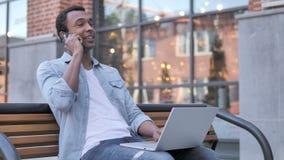 Hombre africano que habla en el teléfono, sentándose en banco almacen de video