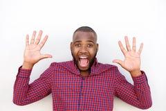 Hombre africano que muestra sus manos y que grita contra la pared blanca Fotografía de archivo libre de regalías