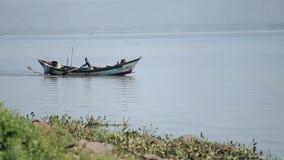 Hombre africano que se sienta en el barco y que rema solamente El pescador está trabajando en el mar almacen de video