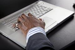 Hombre africano que trabaja en un ordenador Fotos de archivo libres de regalías