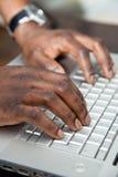Hombre africano que trabaja en un ordenador Fotos de archivo