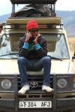 Hombre africano que usa el teléfono en el camión del safari Imágenes de archivo libres de regalías