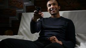 Hombre africano que ve TV, canales cambiantes con teledirigido imagen de archivo libre de regalías