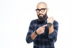 Hombre africano sin pelo en vidrios con la barba que señala en el reloj Fotos de archivo