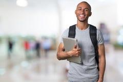 Hombre africano sonriente del estudiante con el ordenador portátil, alameda foto de archivo libre de regalías
