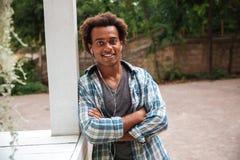 Hombre africano sonriente en los auriculares que se colocan con los brazos cruzados Imágenes de archivo libres de regalías