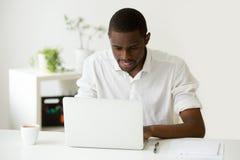Hombre africano sonriente que usa el ordenador portátil que sienta en casa el escritorio de oficina imágenes de archivo libres de regalías