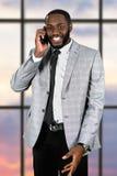 Hombre afro amistoso con el teléfono móvil Foto de archivo libre de regalías