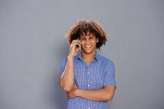 Hombre afro sonriente que habla en el teléfono móvil fotos de archivo libres de regalías