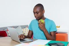 Hombre afroamericano adulto con el ordenador portátil que come la comida sana en el wo Imágenes de archivo libres de regalías