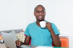 Hombre afroamericano adulto con el ordenador portátil que toma una rotura Fotos de archivo