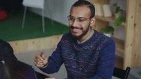 Hombre afroamericano alegre en vidrios que sonríe mientras que discute sobre nuevo proyecto de lanzamiento con el equipo en ofici almacen de video