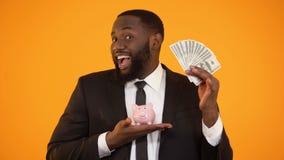 Hombre afroamericano alegre que lleva a cabo el piggybank y que muestra el efectivo del dólar, depósito almacen de metraje de vídeo