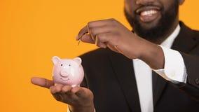Hombre afroamericano alegre que pone monedas en servicio de la hucha, banco de depósito metrajes
