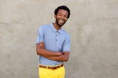 Hombre afroamericano atractivo que sonríe con los brazos cruzados Imagen de archivo