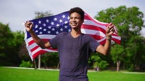 Hombre afroamericano atractivo que sostiene la bandera americana en sus manos en caminar trasero en el campo verde y la sonrisa metrajes