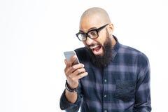 Hombre afroamericano chocado que usa el teléfono móvil y el grito Imágenes de archivo libres de regalías