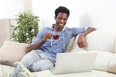 Hombre afroamericano con el ordenador portátil Fotografía de archivo