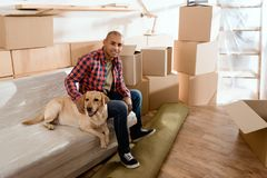 hombre afroamericano con el perro de Labrador en el nuevo apartamento imágenes de archivo libres de regalías