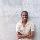 Hombre afroamericano confiado que sonríe con los brazos cruzados Imágenes de archivo libres de regalías