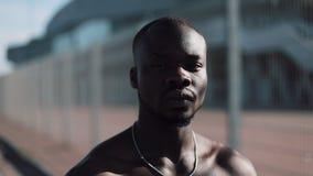 Hombre afroamericano confiado y enojado que mira la cámara - al aire libre Traficante de drogas, preso o situación criminal del h metrajes