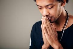Hombre afroamericano de rogación que espera mejor El pedir dios buena suerte fotografía de archivo