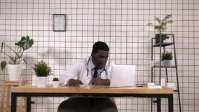 Hombre afroamericano del doctor que parece subrayado y nervioso con las manos en la cabeza almacen de video