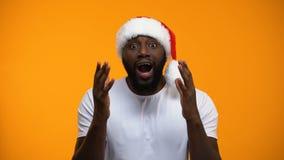 Hombre afroamericano emocionado en el sombrero de Papá Noel, magia de la Navidad, fondo amarillo metrajes