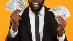 Hombre afroamericano emocionado en el traje que lleva a cabo manojos de dólares, subida de la paga, sueldo almacen de metraje de vídeo