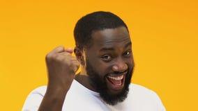 Hombre afroamericano emocionado que muestra sí el gesto, ganador de lotería feliz, cierre para arriba almacen de video