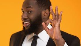 Hombre afroamericano en el gesto aceptable de la demostración del traje, proyecto de inversión rentable almacen de metraje de vídeo
