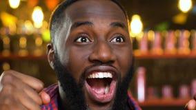Hombre afroamericano en el pub extremadamente feliz sobre la victoria preferida del equipo de deportes metrajes