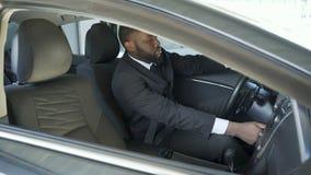 Hombre afroamericano en el traje costoso que sujeta y que gira la ignición de su coche metrajes