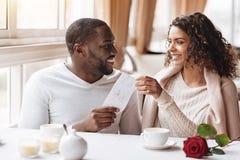 Hombre afroamericano encantado que da un presente a la mujer Imagen de archivo libre de regalías