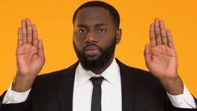 Hombre afroamericano estricto en el gesto de la parada de la demostración del traje, protección de los derechos laborales almacen de video