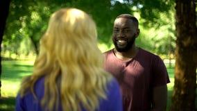 Hombre afroamericano extremadamente feliz que mira a la muchacha querida, preparando sorpresa fotos de archivo libres de regalías