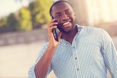 Hombre afroamericano feliz que habla en el teléfono Imagen de archivo libre de regalías