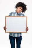 Hombre afroamericano feliz que lleva a cabo al tablero en blanco Imagen de archivo libre de regalías
