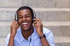 Hombre afroamericano feliz que ríe con los auriculares Fotos de archivo